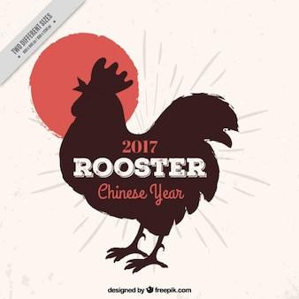 雄鶏のシルエットを持つ中国の新年の背景