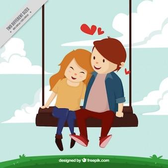 ブランコに乗って愛で素敵な若いカップルの背景