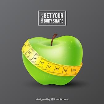 テープのメジャーと緑のリンゴの背景
