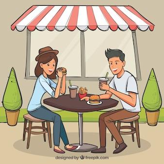屋外でハンバーガーを食べる手描きの若いカップル