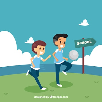 Счастливые школьные друзья, играющие в футбол