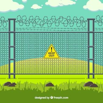 緑色の景観の有刺鉄線のある金属フェンス