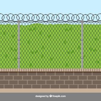 Металлический забор с колючей проволокой с травой