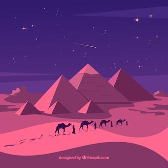夜のキャラバンとピラミッドの風景