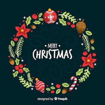 手はクリスマスの花輪の背景を描いた