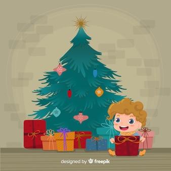 クリスマスツリーの背景で幸せな子供