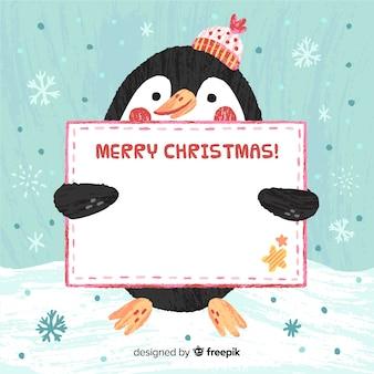 空白のサインの背景を持つペンギン