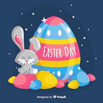 夜のイースターの日の背景に卵と描かれたウサギを手します。