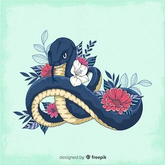 Ручной обращается змея с цветами фона