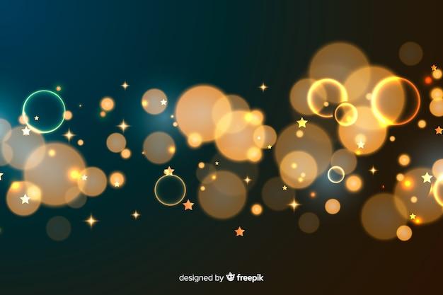 金色の粒子のボケ味の装飾的な背景