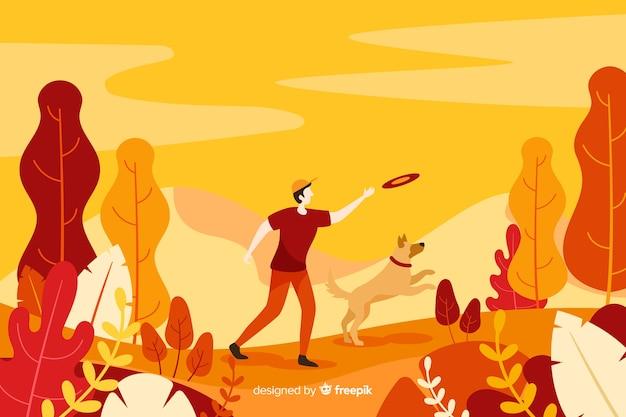 秋の背景に彼の犬と遊ぶ男