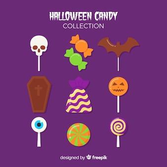 紫色の背景にハロウィーンのキャンディーをトリックまたは治療