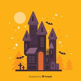 オレンジ色の背景の色合いの平らなハロウィーンの家