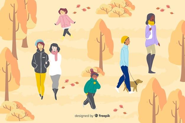秋の公園を歩いているさまざまな人々