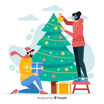 屋外のクリスマスツリーを飾る人々