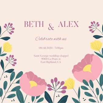 パステルピンクの花で描かれた結婚式招待状を手します。