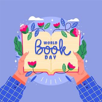 花を持つ開いた本を持っている人と世界本の日