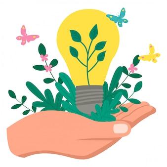 緑のエコロジー電球と緑の植物を持っている手