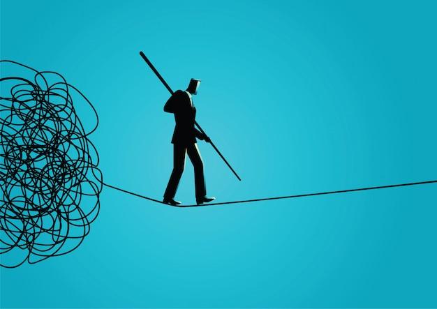 絡み合ったロープから慎重に歩いているビジネスマン