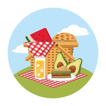 テーブルクロスにスイカとサンドイッチの食べ物を入れたバスケット