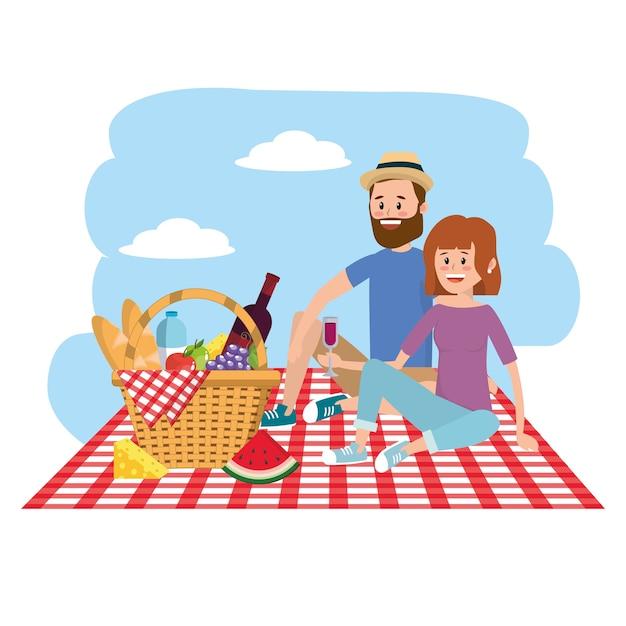 自然の女性と男はテーブルクロスのバスケットとカップル