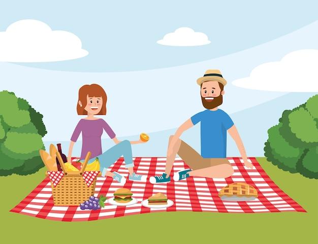 楽しい女性と男カップルのテーブルクロスでバスケット