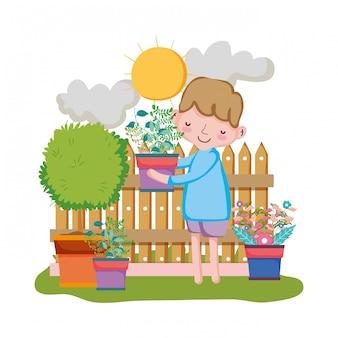庭のフェンスでハウスプラントを持ち上げている少年