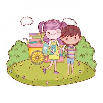 Счастливые маленькие дети с тележкой книг в ландшафте