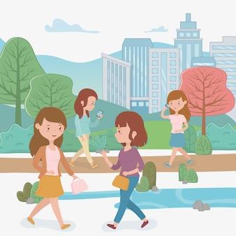 Красивые женщины гуляют в парке с помощью смартфонов