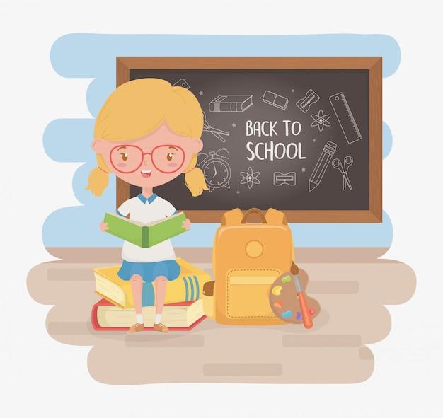 黒板と学用品の小さな学生の女の子