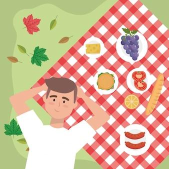 ブドウとテーブルクロスの中にスナック食品を持つ男