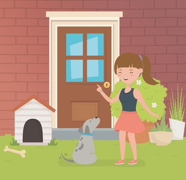 家の庭で小さな犬のマスコットを持つ若い女