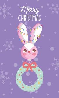 ライトと花輪のクリスマスカードとウサギ