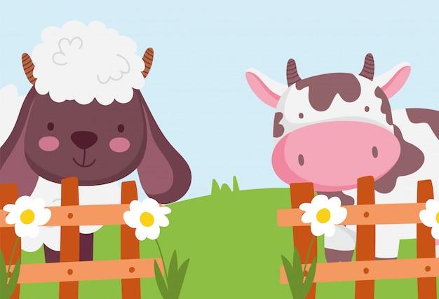 牛と羊の木製のフェンスの花農場の動物