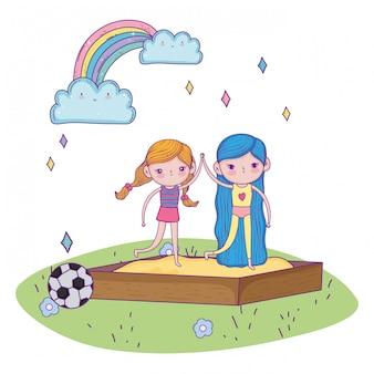 幸せな子供の日、サンドボックスの遊び場で手を繋いでいる少女