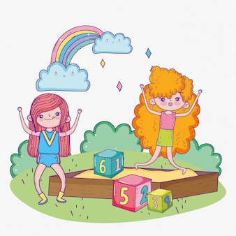 Счастливый детский день, девочки играют в песочнице с парком блоков