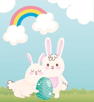 フィールドの虹の空の装飾に緑の卵とハッピーイースターの白いウサギ
