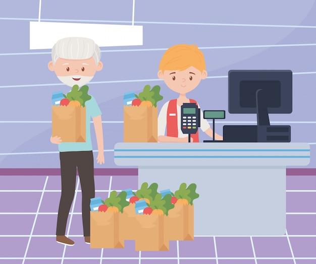 多くの食料品の紙袋を待っている老人がレジでの支払いを超過購入