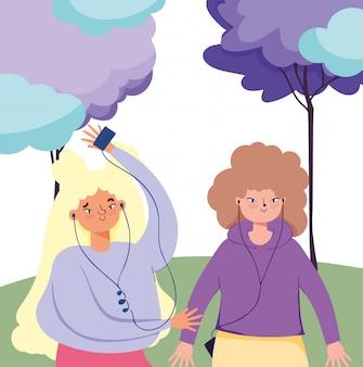 Девушки слушают музыку со смартфоном и наушниками в парке
