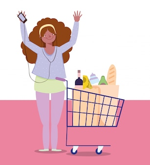 音楽を聴く、ショッピングカート食品スーパーマーケットの女性
