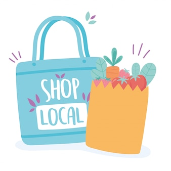 地元のビジネスをサポートし、小さな市場のエコと食料品の入った紙袋を買う