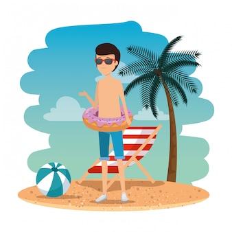 サングラスとビーチでフロートドーナツを持つ若い男