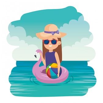 海の上のフランドルフロートとビーチの風船を持つ少女