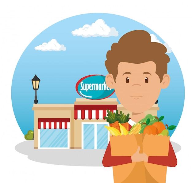 買い物袋でスーパーマーケットの食料品を持つ男