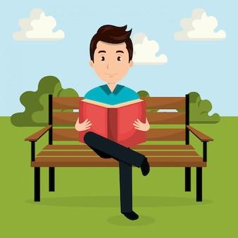 若い男が公園のキャラクターで本を読んで