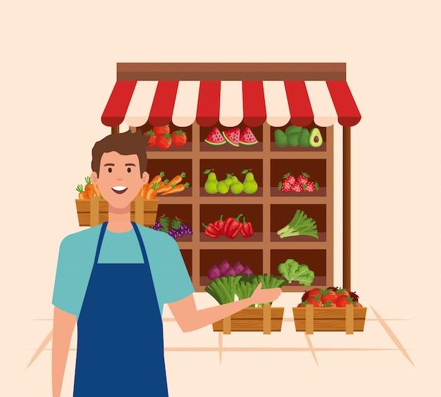 Продавец в фартуке со свежими овощами и фруктами