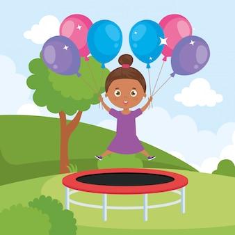 Маленькая девочка афро в прыжке на батуте с воздушными шарами гелия в ландшафтном парке