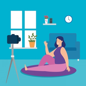 リビングルームでオンラインヨガの練習の女性