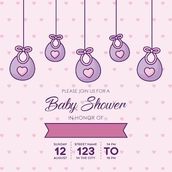 ピンクの背景、カラフルなデザインの上にぶら下がっている装飾的なビブとベビーシャワー招待状テンプレート。