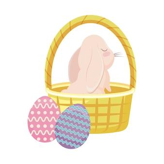 バスケットの枝編み細工品とイースターの卵のかわいいウサギ